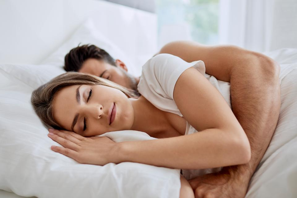 Side view of young woman sleeping on her side while her husband is hugging her