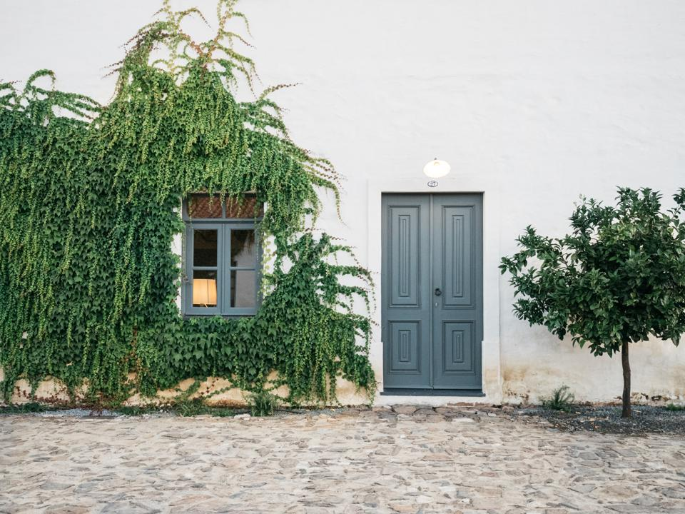 The cottages at São Lourenço do Barrocal in Portugal have blue doors and vines.
