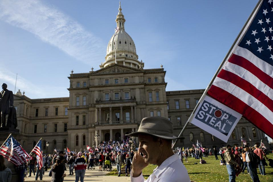 A man stands in front of the Michigan State Capitol Building...