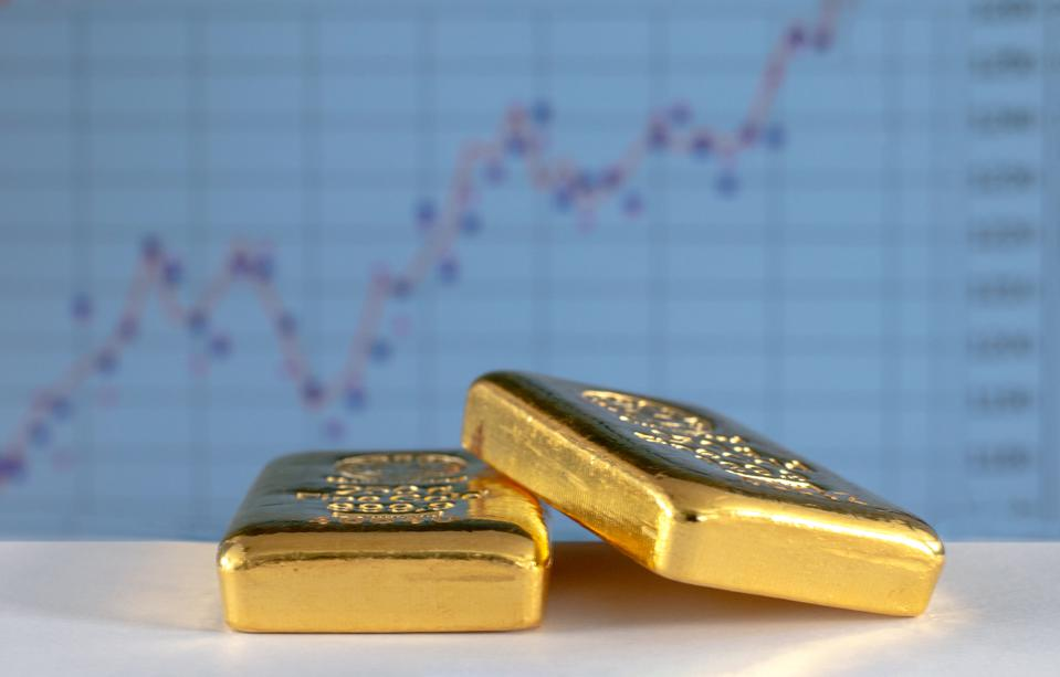 Gold bullions on the background of the growth chart.