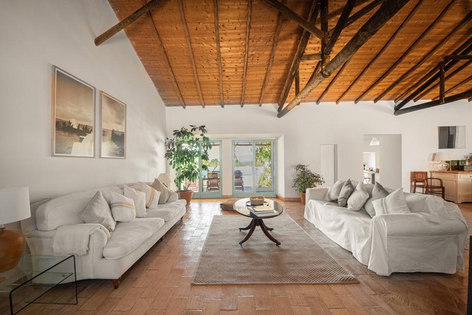 There are overstuffed white couches on a terra-cotta floor in the house in the Algarve