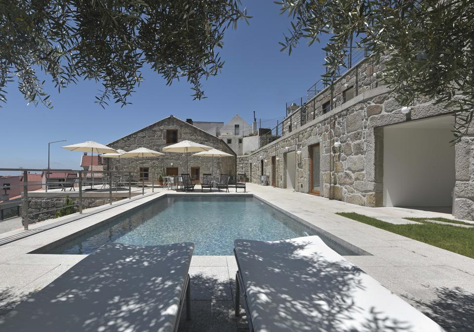 The swimming pool at Casas da Lapa hotel in Portugal is in front of a stone building.