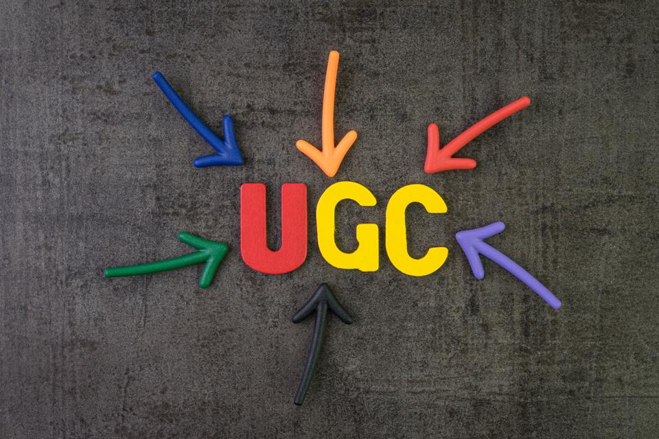 UGC, User generated content using in brand communication online advertising concept, multi color arrows pointing to the word UGC at the center of black cement chalkboard wall