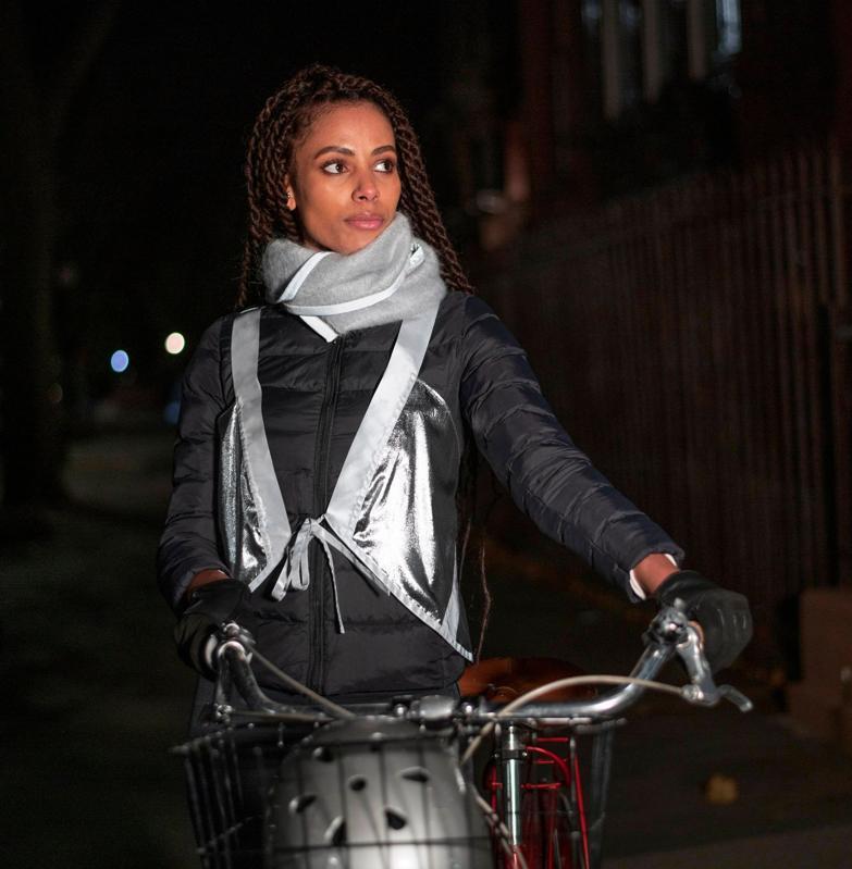 A woman wearing reflective gear on a bike.