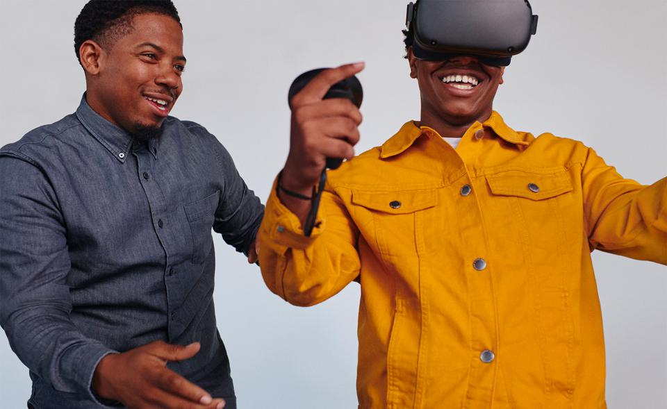 Two Black men in a marketing image, with one wearing an Oculus headset.