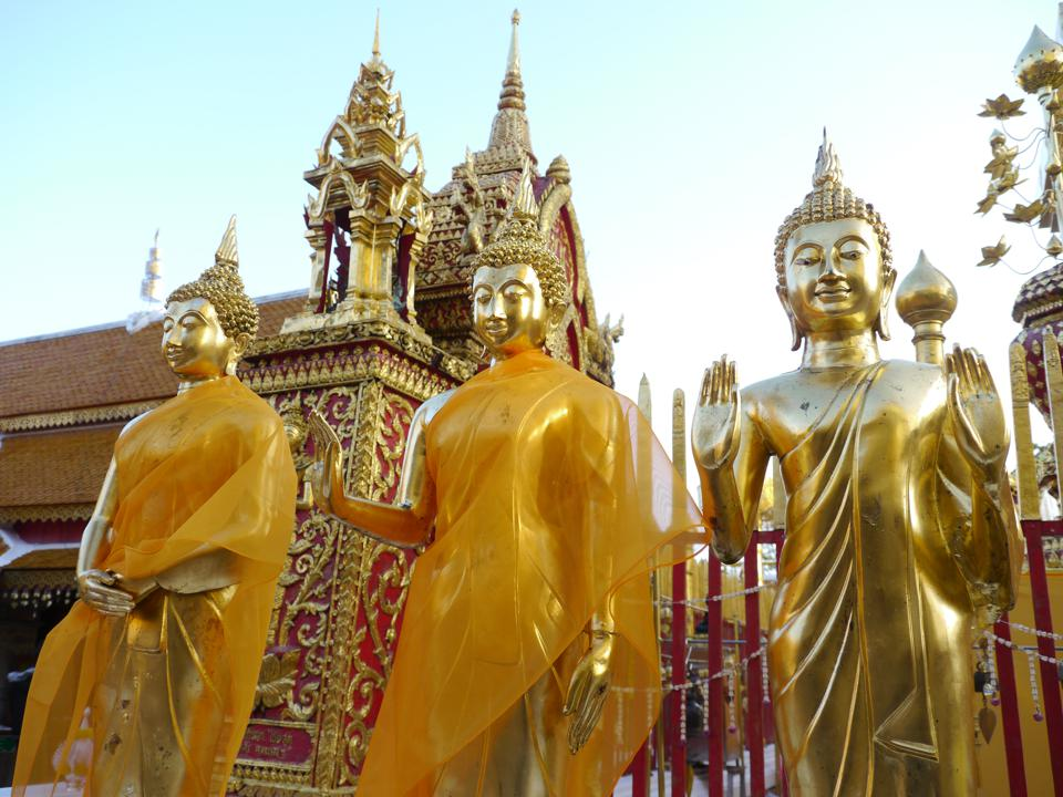 Three gold Buddha statues, two draped in orange and two with hands raised, in front of a gold and red temple