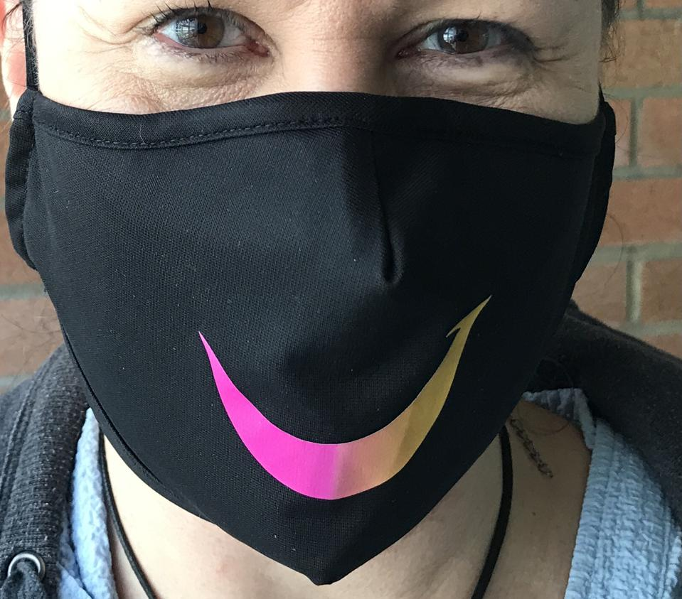 A woman wearing a black mask with a colorful stylized T that looks like a smile