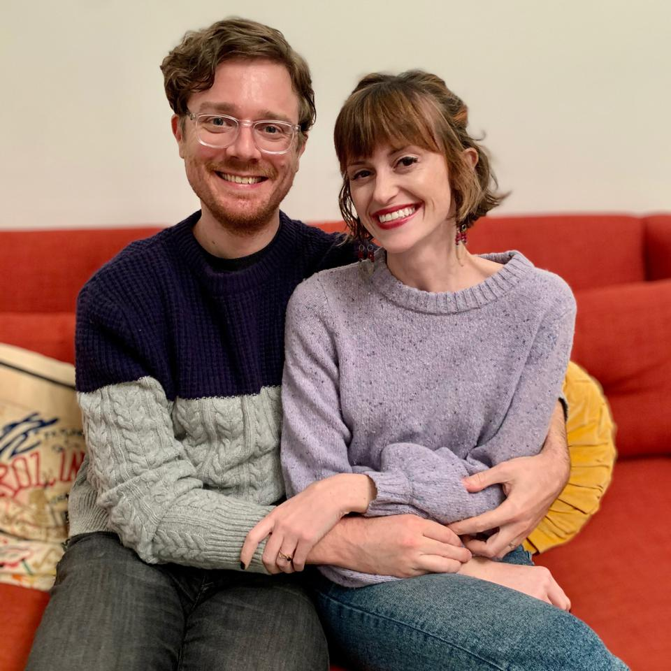 A couple sits on an orange sofa.