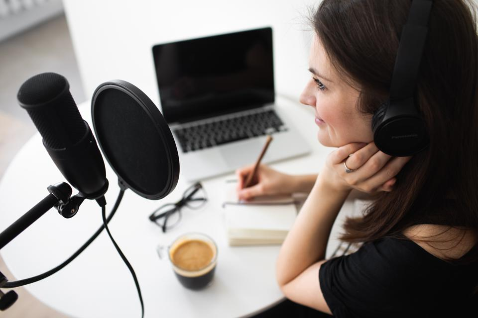Young woman in black headphones reading notes aloud and making recordings podcast while sitting at table at home. Blogger concept.