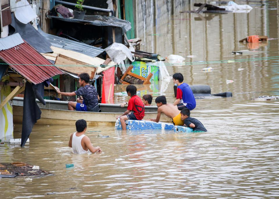 Residents seen in a homemade rescue boat in a flooded street...
