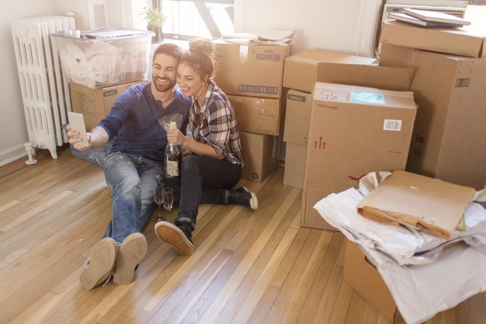 Moving house: Young couple sitting in room full of boxes, holding champagne bottle, taking self portrait with smartphone