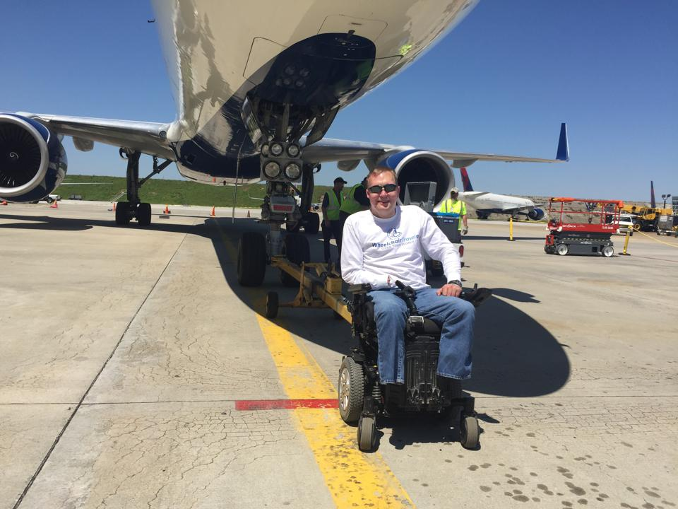 John Morris in his wheelchair in front of an aircraft