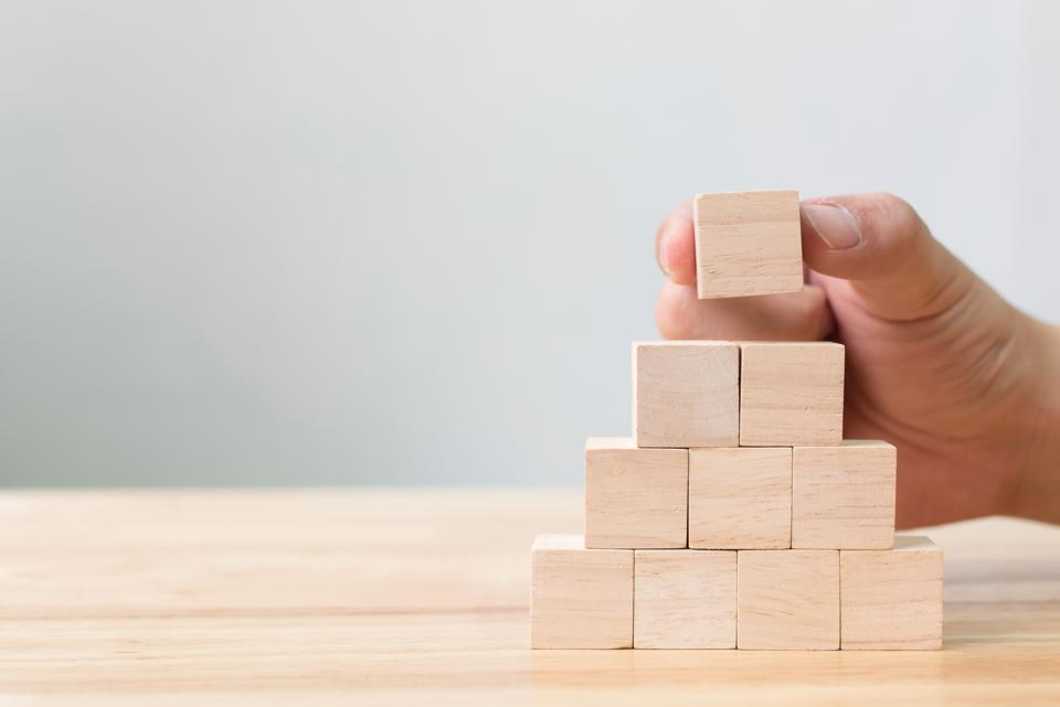 Cropped Hands Of Person Stacking Wooden Blocks On Table