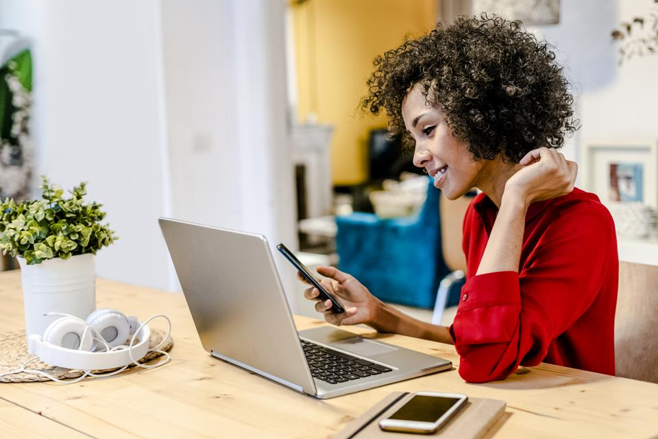 Smiling woman using laptop and cell phone at table