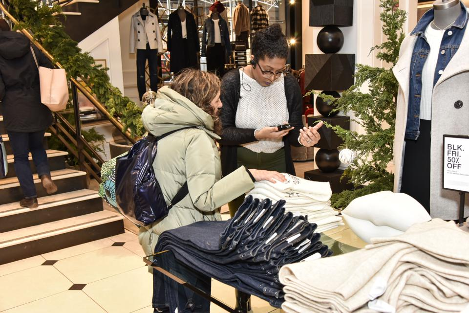 A shopper in a Banana Republic store is being helped by a sale associate