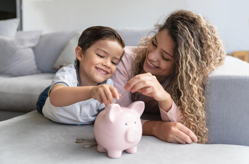 Happy mother and son saving money in a piggybank