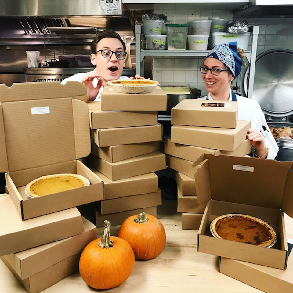 Piles of pie boxes and a man and a woman peering over them.