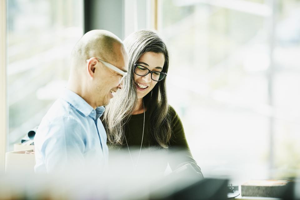 Smiling coworkers looking at data on digital tablet in office