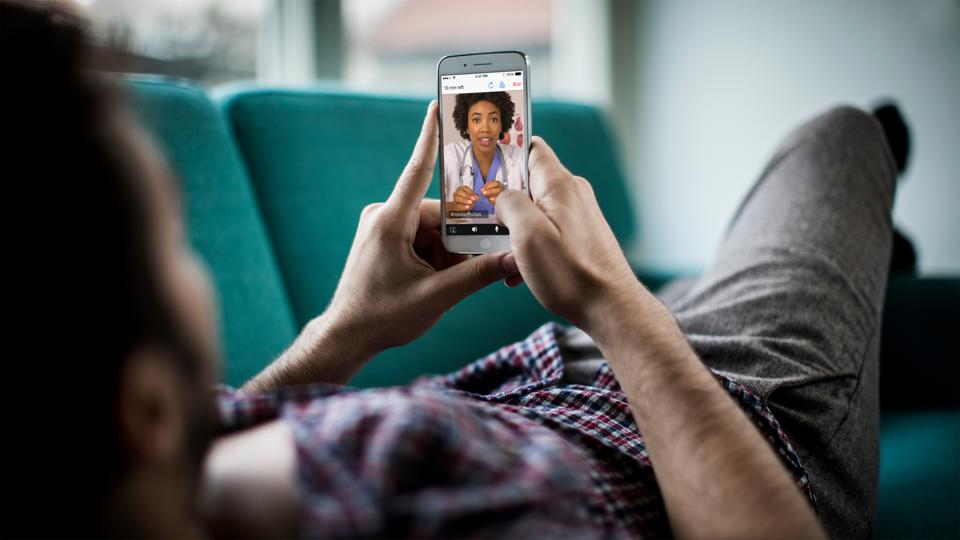 Man on couch doing telehealth appointment on phone