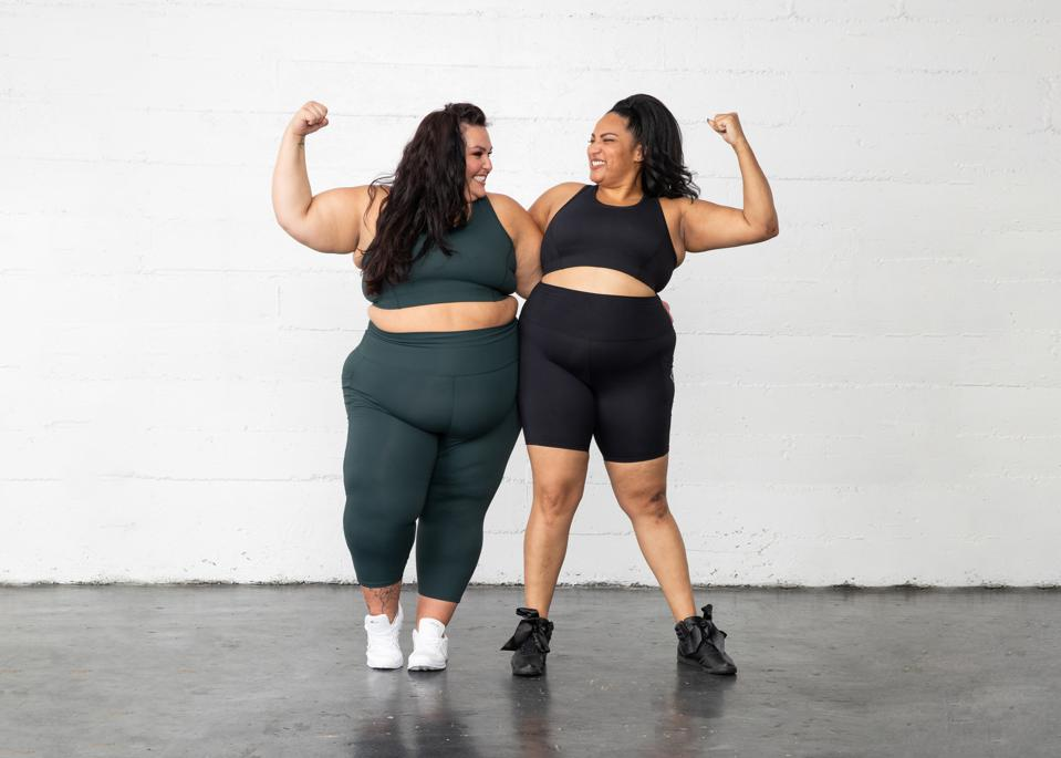 Two women wearing athletic wear smile and flex their arms