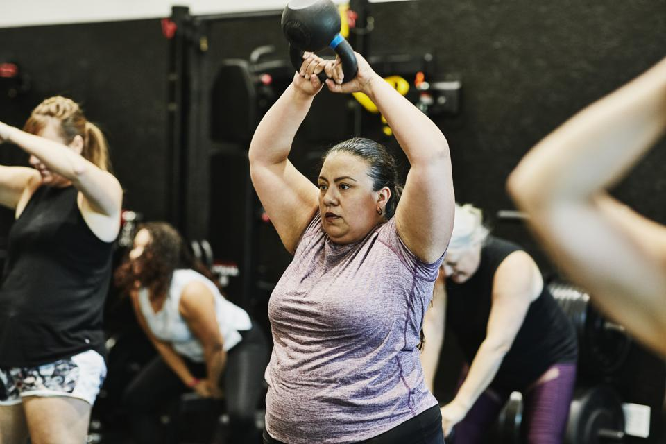 Woman doing kettlebell swings while working out during class in gym