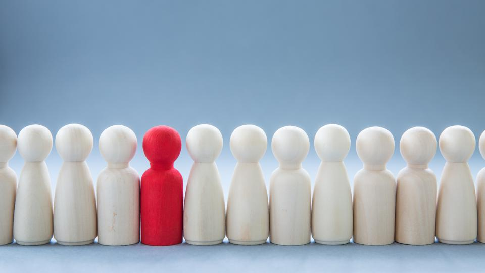 A lone red figure standing out among white ones in a line.