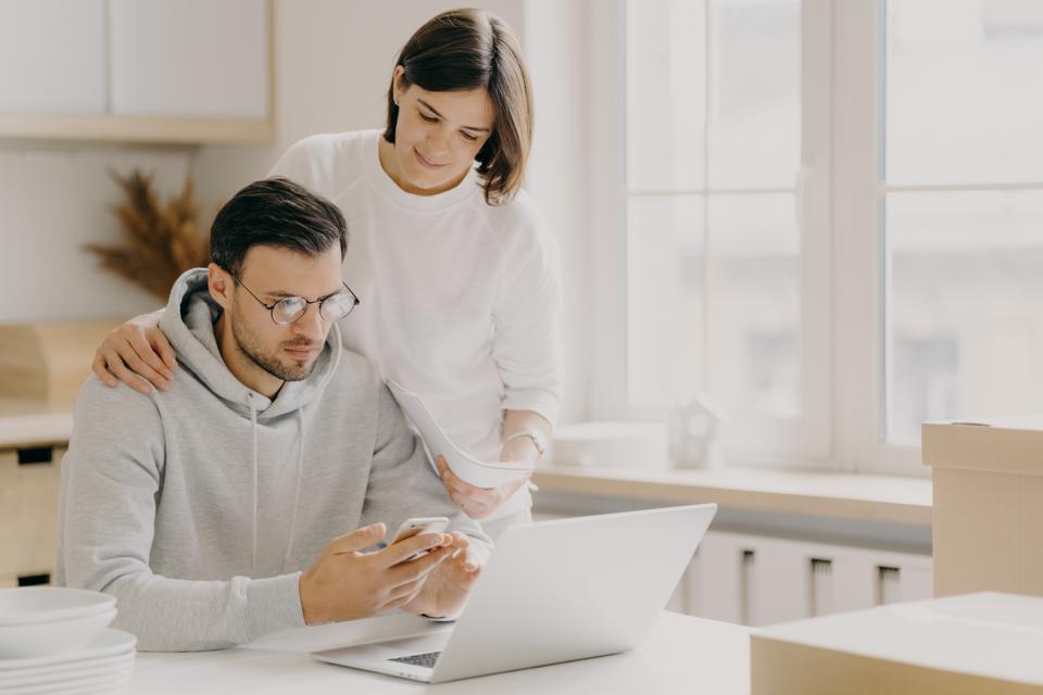 Couple Using Laptop Phone