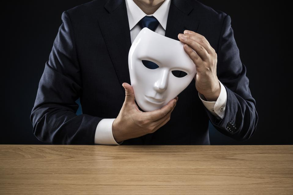 Man in a suit removes his mask