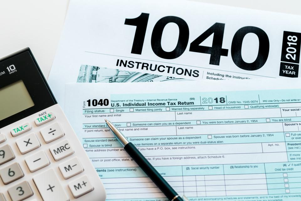 New 2019 IRS 1040 tax form, instructions, pen and calculator