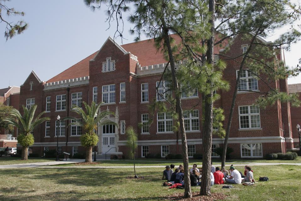 Students sitting outside Keene-Flint Hall at the University of Florida.