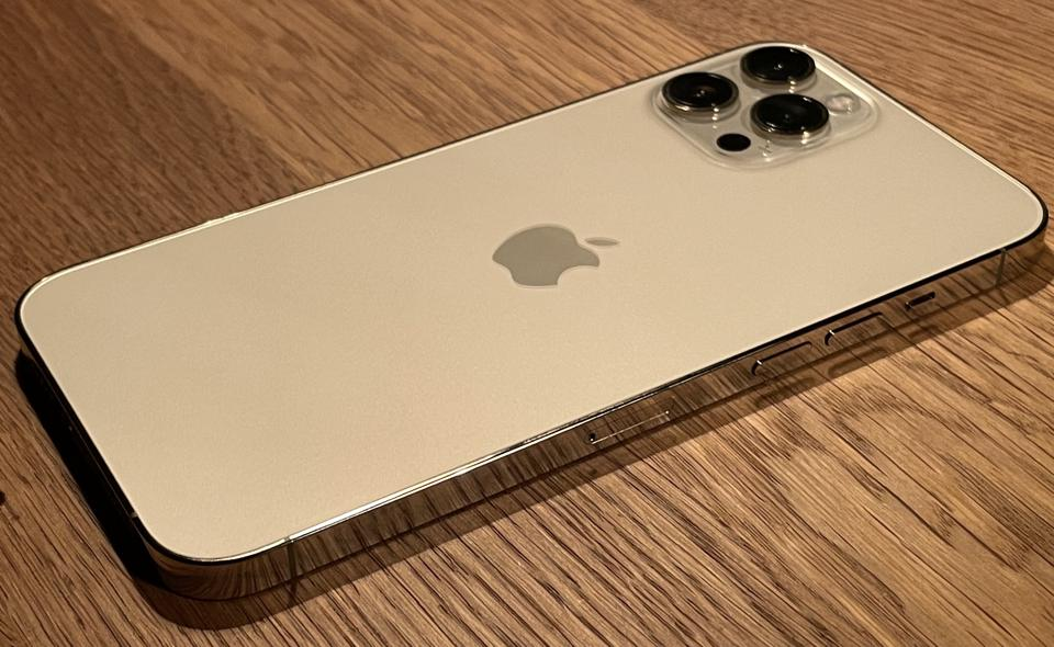 Apple iPhone 12 Pro Max in gold finish, which seems to change color according to the light.