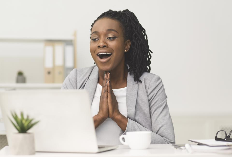 Happy Black Office Girl Clasping Hands Sitting At Workplace
