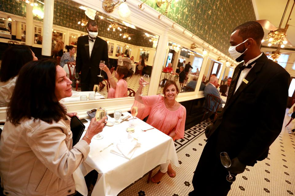 Diners in the gold and green wallpapered main dining room at New Orleans' iconic restaurant Galatoire's