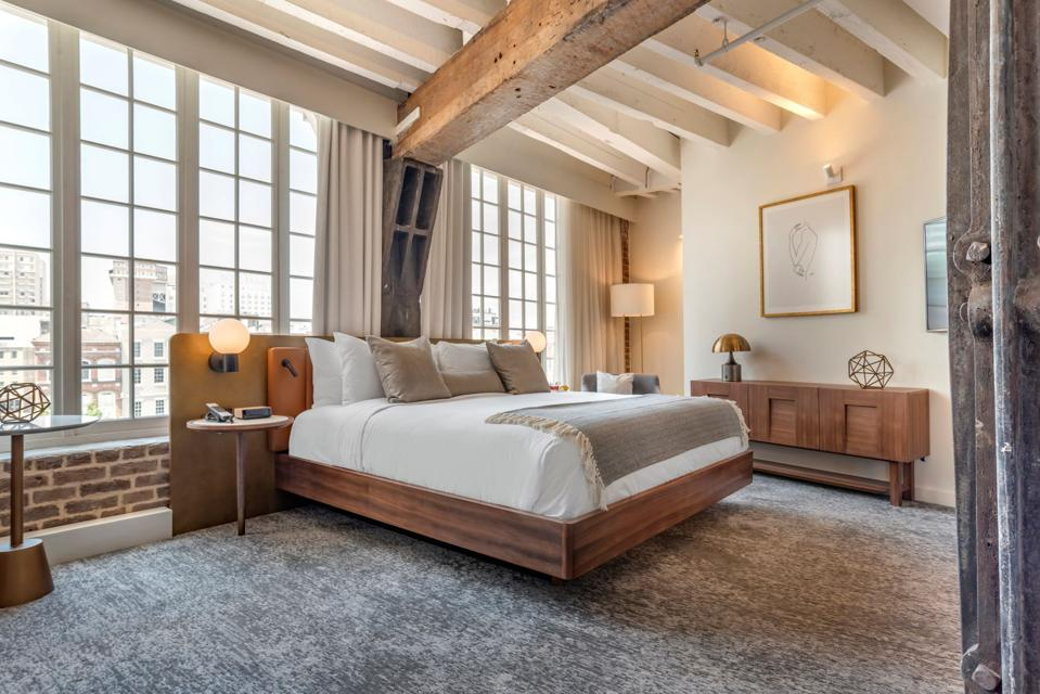 A contemporary hotel guest room with exposed brick walls and wooden ceiling beams