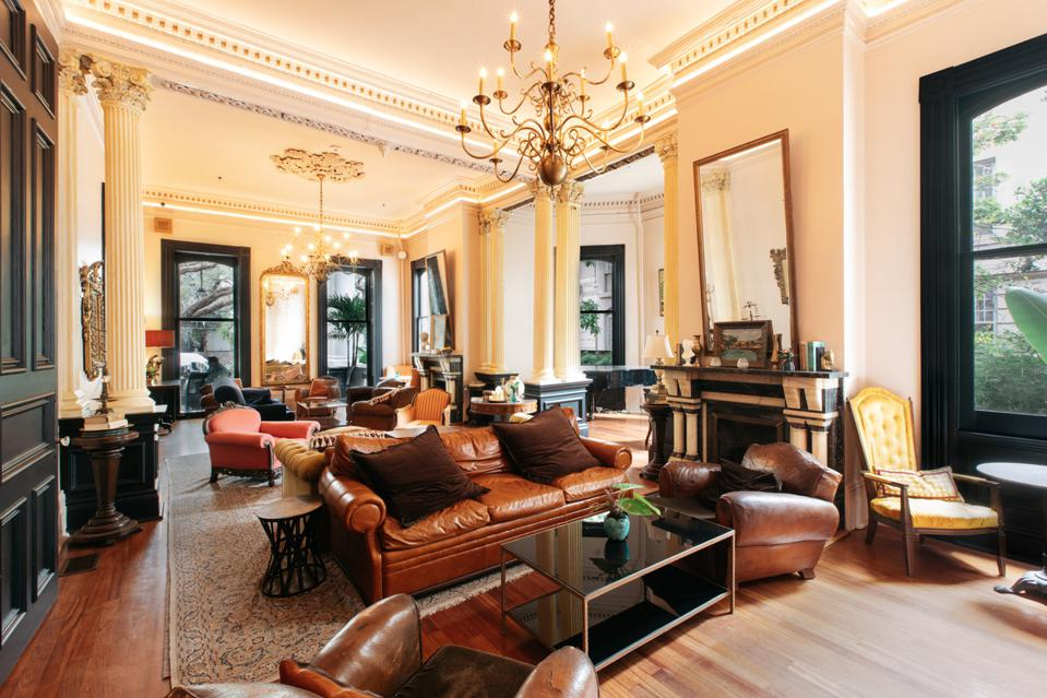 A large room with a golden chandelier, carved moldings and an array of eclectic furniture including leather chairs and couches and velour armchairs