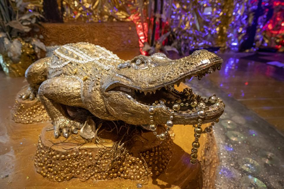 A gold alligator draped in gold beads