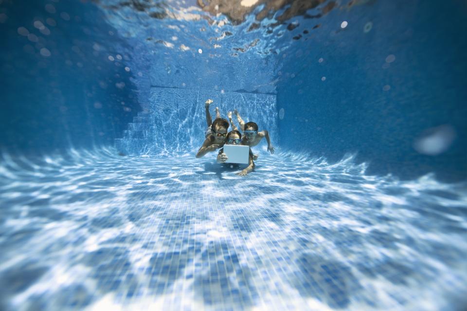 Kids playing tablet underwater