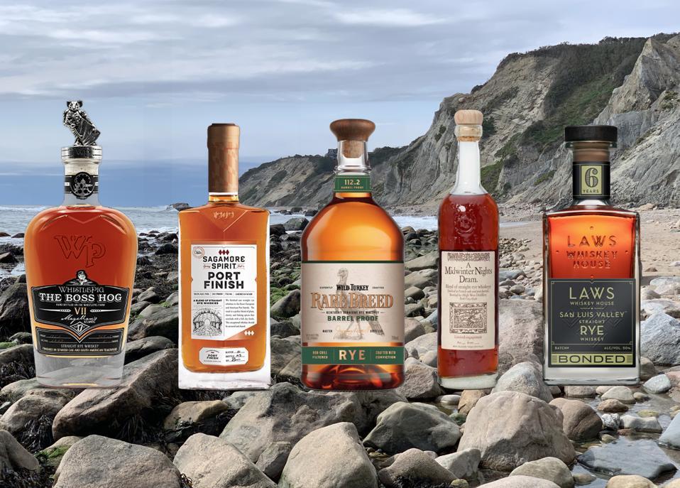 Five bottles of high end rye whiskey sit on a beach in Block Island, Rhode Island