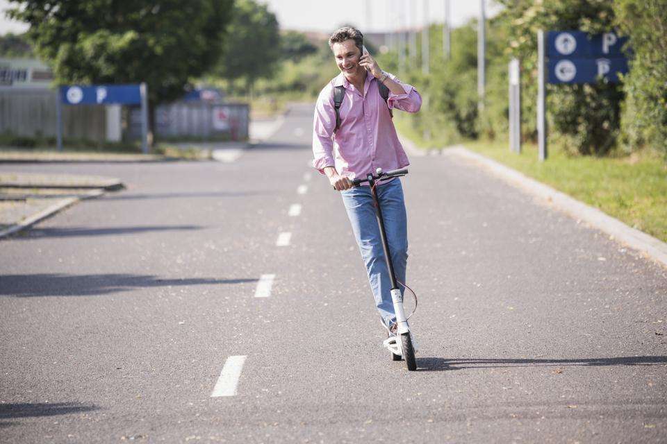 Businessman using smartphone riding his E-Scooter