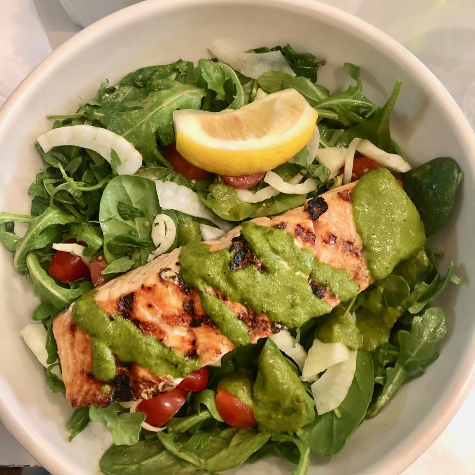 salmon over leafy green salad