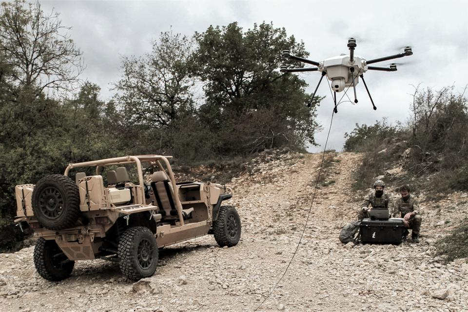 Two operators control a tethered Orion 2 drone in an arid environment.
