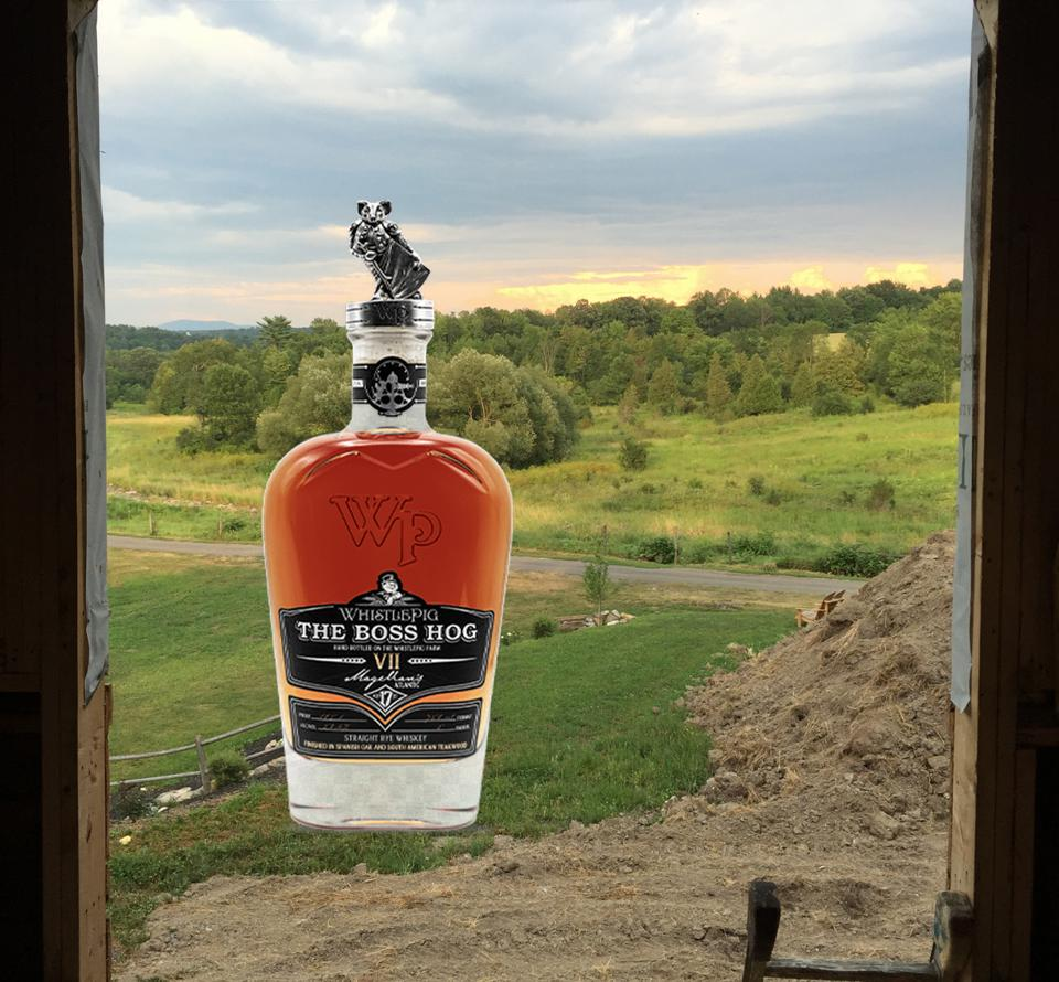 A bottle of premium WhistlePig rye whiskey sits outside of a Vermont barn.