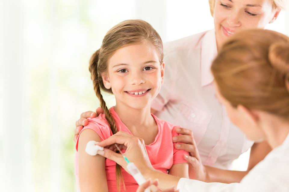Doctor giving injection to little girl