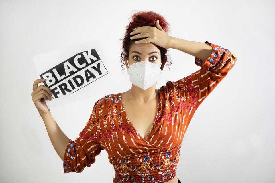 Girl wearing a mask amazed with wide eyes with one hand on her head and holding a black friday sign with the other hand. Young woman with white skin and curly red hair dressed in colorful patterned clothing