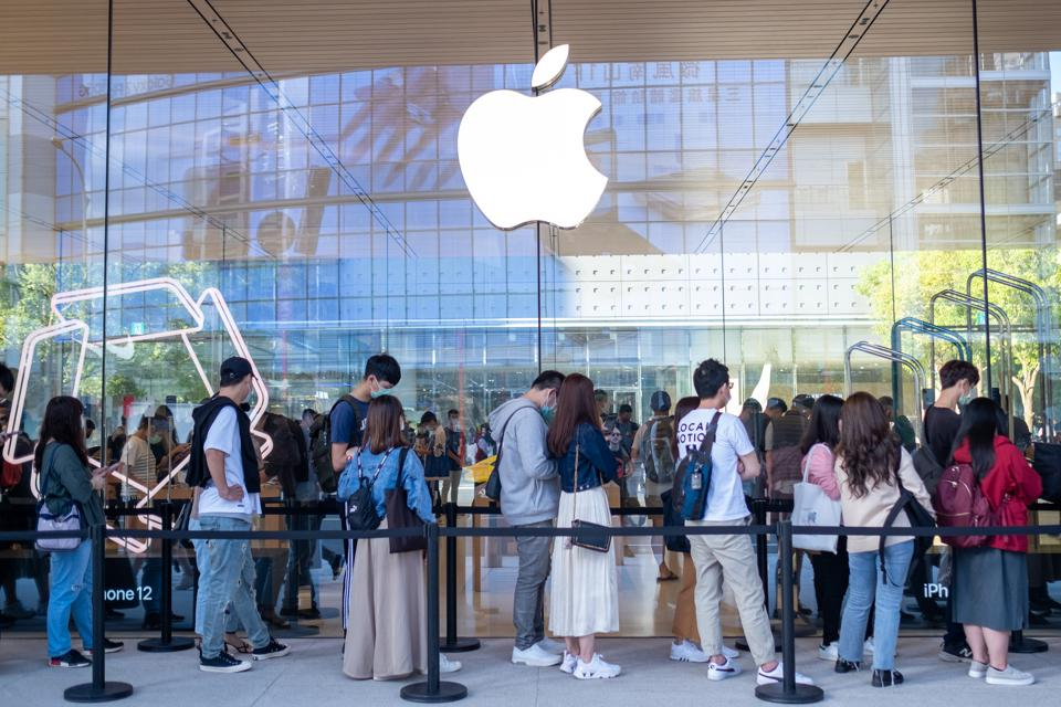 People wearing face masks line up at an Apple store in...
