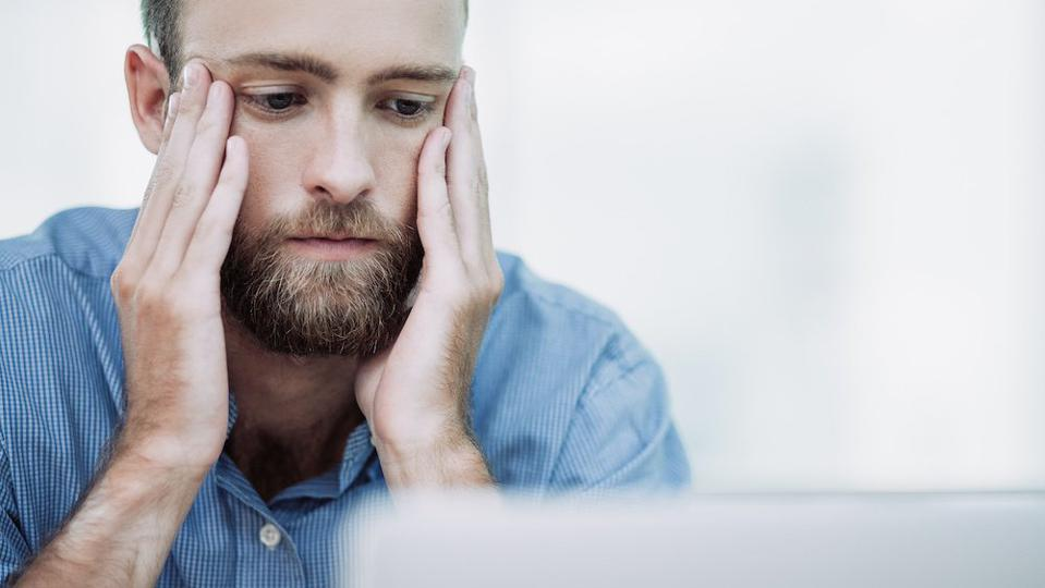 Worried young man looking at laptop