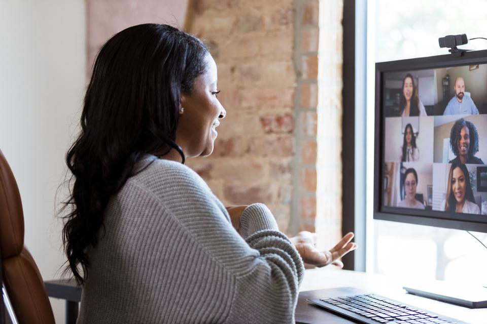 Cheerful woman video chats with colleagues