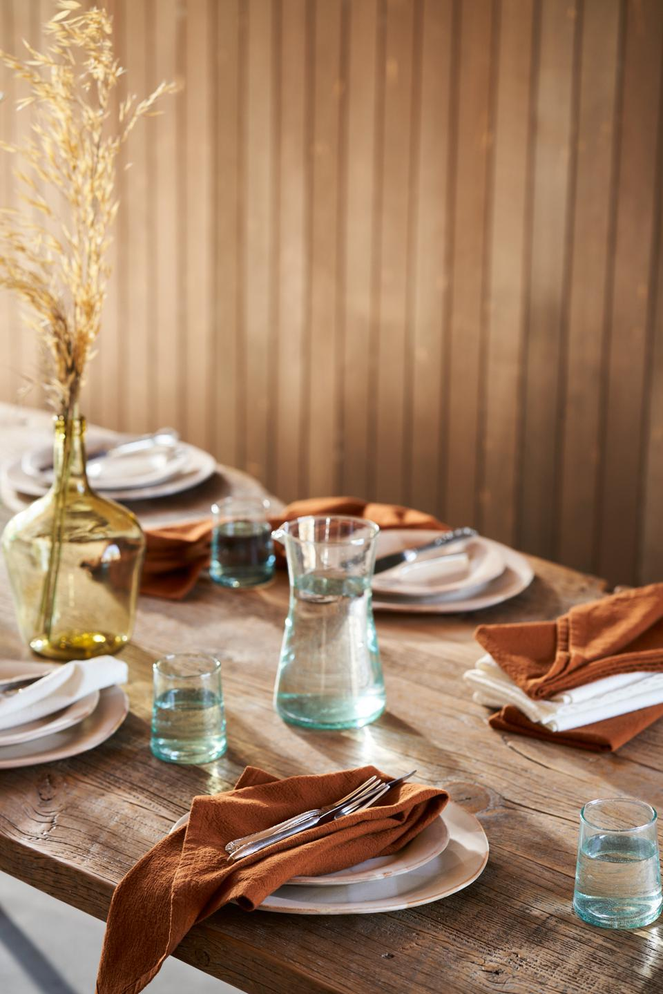 Rust-colored organic napkins within an elegant table setting.