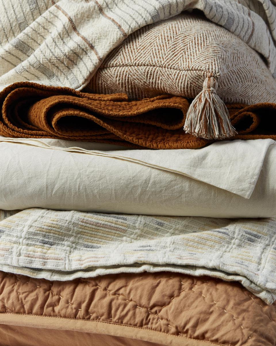 A stack of blankets and sheets in ivory and rust hues.