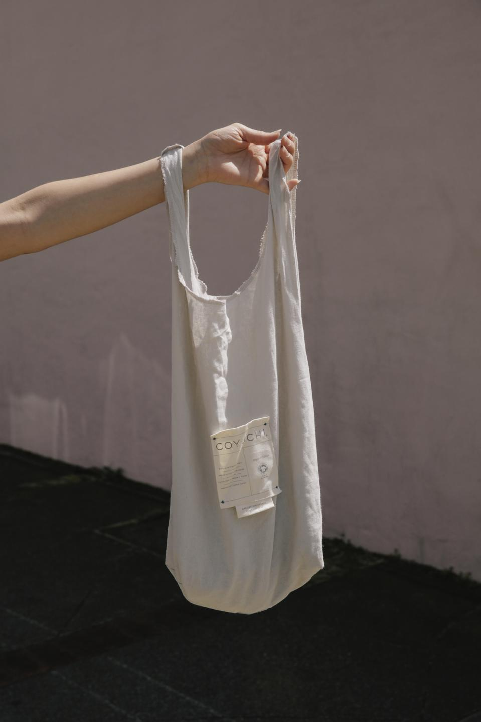 A white organic cotton bag with Coyuchi on it.